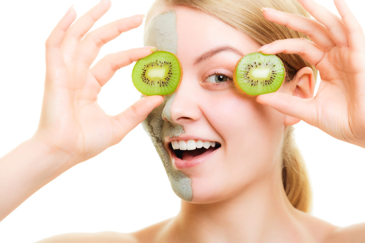 Skin care. Woman in clay mud mask on face holding slices of kiwi fruit isolated. Girl taking care of dry complexion.